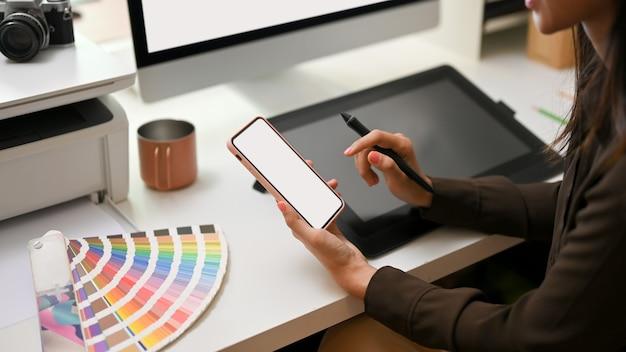 Seitenansicht des weiblichen grafikdesigners unter verwendung des modell-smartphones beim sitzen am büroschneid-beschneidungsweg