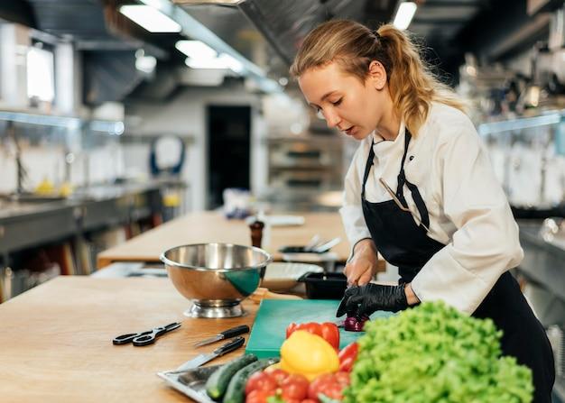 Seitenansicht des weiblichen kochs, der salat mit gemüse vorbereitet