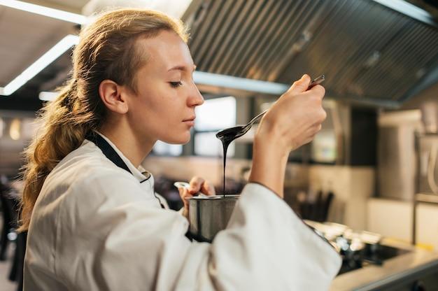 Seitenansicht des weiblichen kochs, der soße versucht