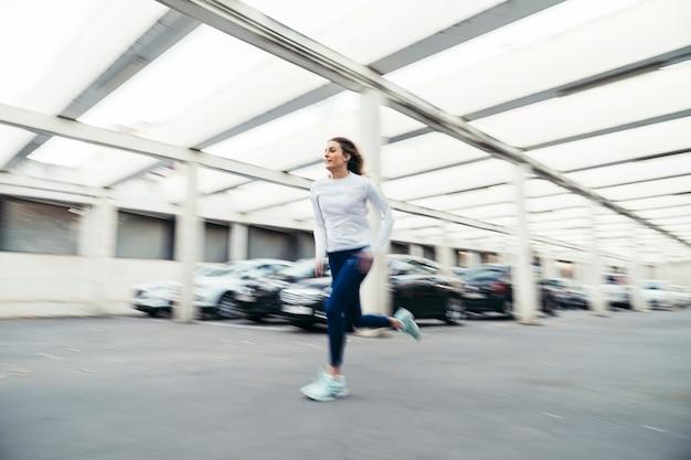 Seitenansicht des weiblichen läufers laufend unter eine struktur mit autos im hintergrund