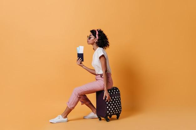 Seitenansicht des weiblichen touristen, der auf koffer sitzt