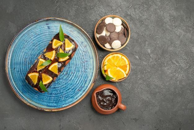 Seitenansicht des weichen kuchens verziert mit zitrone und schokolade auf dunklem tisch