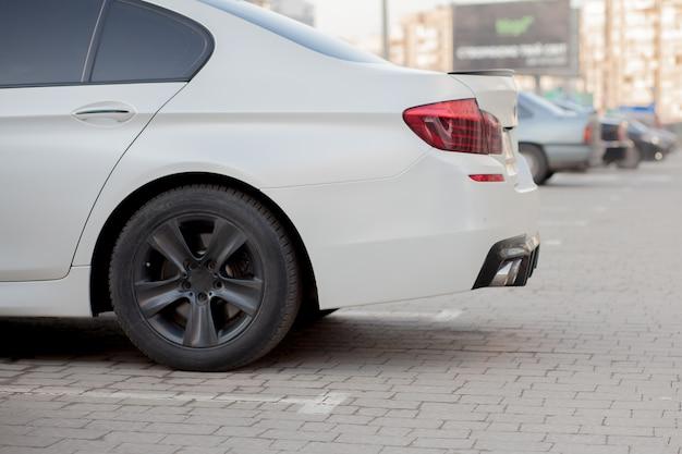 Seitenansicht des weißen autos, das im gepflasterten parkplatzbereich auf unscharfem vorortstraßenhintergrund an hellem sonnigem tag geparkt wird. transport- und parkkonzept