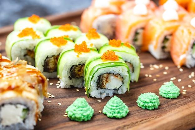 Seitenansicht drachenrolle mit gurken gebratenem fisch tobiko kaviar sesam und wasabi auf einem brett