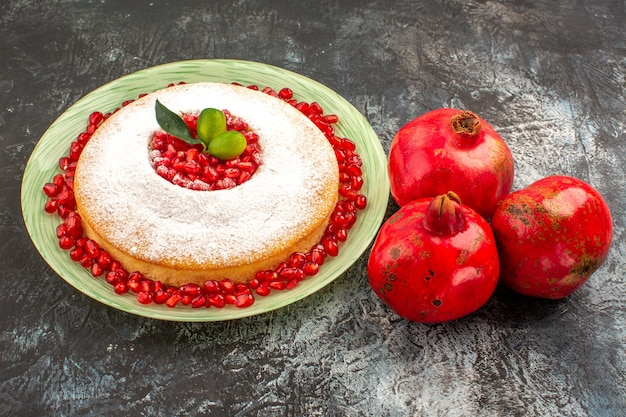 Seitenansicht ein appetitlicher kuchen ein appetitlicher kuchen mit granatapfelkernen und drei granatäpfeln