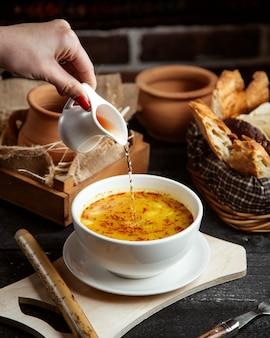 Seitenansicht ein mädchen gießt essig in eine teller-dushbara-suppe ein traditionelles aserbaidschanisches gericht