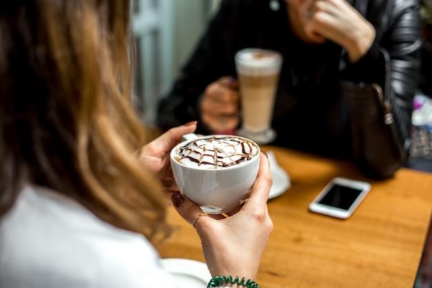Seitenansicht ein mädchen trinkt cappuccino