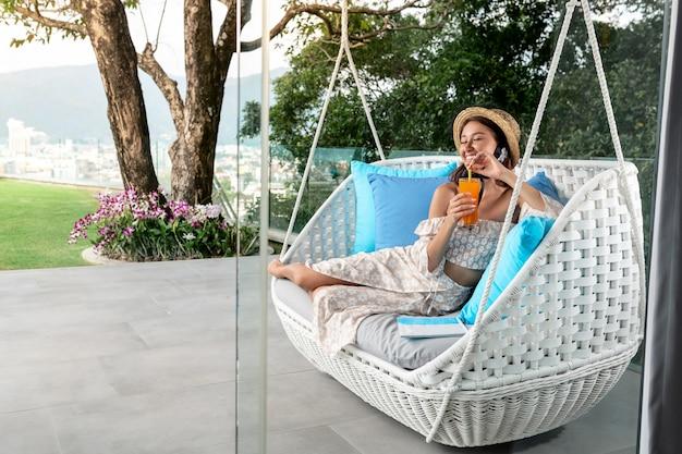 Seitenansicht: ein modellmädchen im strohhut hält tropencocktail der frischen frucht mit orange im hohen glas, das auf sofa gegen tropischen hintergrund sitzt