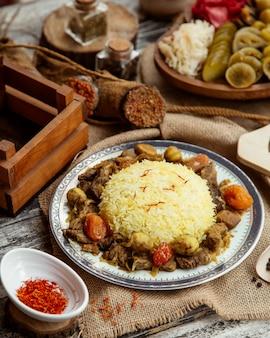 Seitenansicht ein traditionelles aserbaidschanisches gericht pilaw mit fleisch und süßigkeiten mit gewürzen und gesalzen