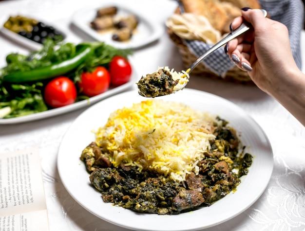Seitenansicht eine frau, die ein traditionelles azerbaijanisches gericht shabzi pilaw gebratenes fleisch mit gemüse und gekochtem reis mit gemüse und kräutern isst