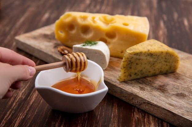 Seitenansicht eine frau hält eine holztasche mit honig mit einer untertasse mit verschiedenen käsesorten auf einem ständer auf einem hölzernen hintergrund
