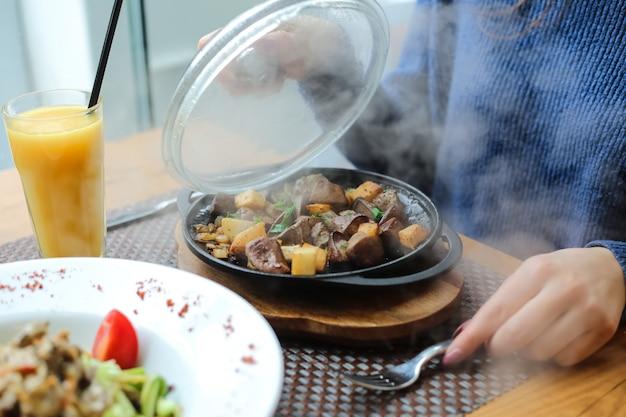 Seitenansicht eine frau öffnete den deckel bratkartoffeln mit einer leber in einer pfanne auf einem ständer mit orangensaft auf dem tisch