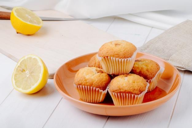 Seitenansicht eine halbe zitrone auf einem brett mit cupcakes auf einem teller