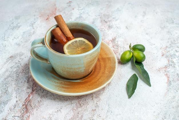 Seitenansicht eine tasse tee tasse kräutertee mit zitronen- und zimtscheiben auf der weißen untertasse mit zitrusfrüchten auf dem rosa tisch