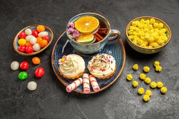 Seitenansicht eine tasse teeschalen mit bunten süßigkeiten neben dem teller eines appetitlichen cupcakes mit sahne und einer tasse tee auf dem tisch