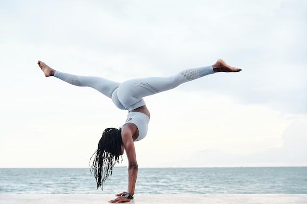 Seitenansicht einer athletischen jungen frau, die yoga praktiziert, handstand mit spagat am strand macht