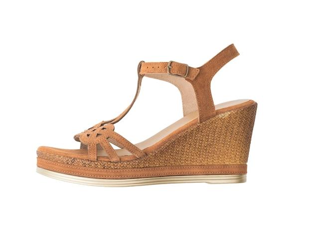 Seitenansicht einer braunen weiblichen sandale auf einem weißen hintergrund. sommerschuhe für frauen.
