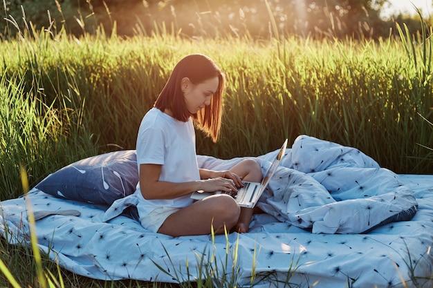 Seitenansicht einer dunkelhaarigen frau, die im freien arbeitet, frau in freizeitkleidung, die den laptop auf den knien hält, freiberuflerin, die ihre arbeit auf der grünen wiese bei sonnenuntergang macht und die natur genießt