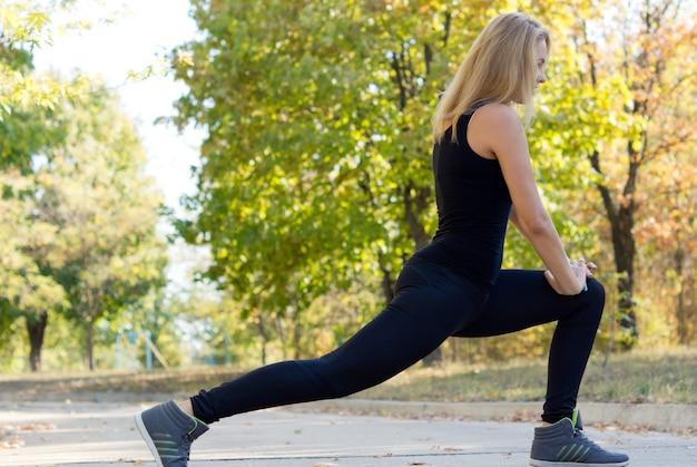 Seitenansicht einer förmigen formschönen jungen blonden frau, die sich während eines trainings in einem park ausdehnt