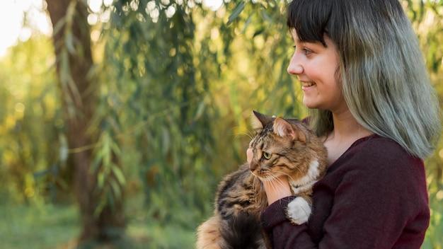 Seitenansicht einer frau des gefärbten haares, die ihre katze der getigerten katze im wald umfasst