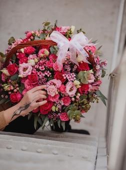 Seitenansicht einer frau, die eine blumenkomposition mit rosa rosen eustoma und eukalyptus in einem weidenkorb hält
