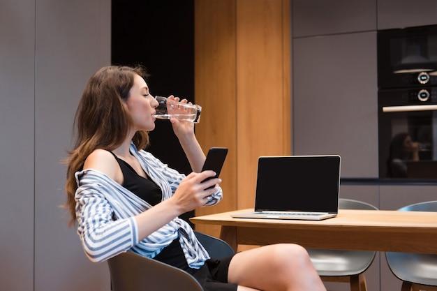 Seitenansicht einer glücklichen frau mit langen braunen haaren, die smartphone hält, während sie klares wasser aus glas trinkt