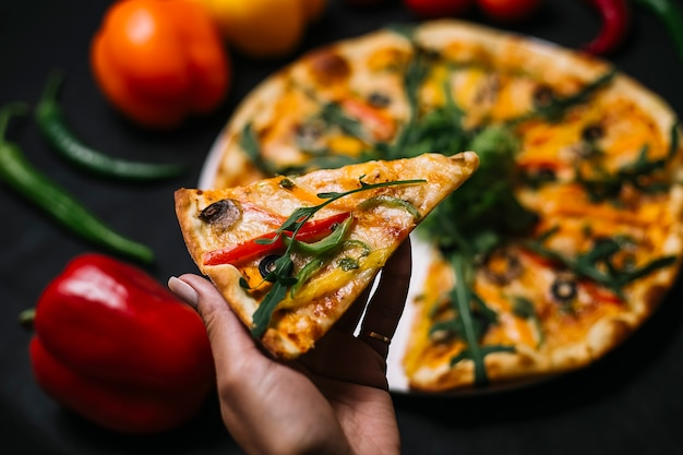 Seitenansicht einer hand, die ein stück italienische pizza mit bunten paprikapilzen, schwarzen oliven, urugula und käse hält