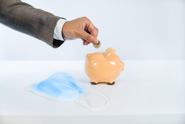 Seitenansicht einer hand, die eine münze in ein keramisches sparschwein mit weißem hintergrund und sehr gutem licht und einer gesichtsmaske aufgrund der covid19-coronavirus-pandemie einführt
