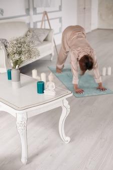 Seitenansicht einer hübschen frau im schlafanzug, die morgens zu hause yoga in ihrem zimmer praktiziert. gesundes lebensstilkonzept. morgenfitness