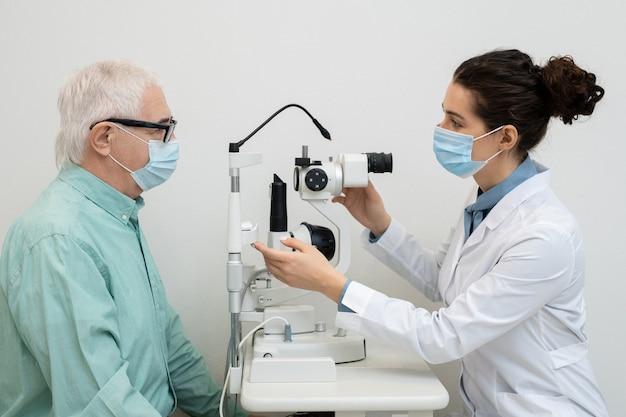Seitenansicht einer jungen augenärztin, die medizinische geräte in kliniken verwendet, während sie das sehvermögen eines älteren männlichen patienten in schutzmaske testet