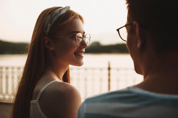 Seitenansicht einer jungen charmanten rothaarigen frau mit sommersprossen lächelnd, die ihren freund lächelnd betrachten. romantisches paar, das draußen gegen sonnenuntergang datiert.