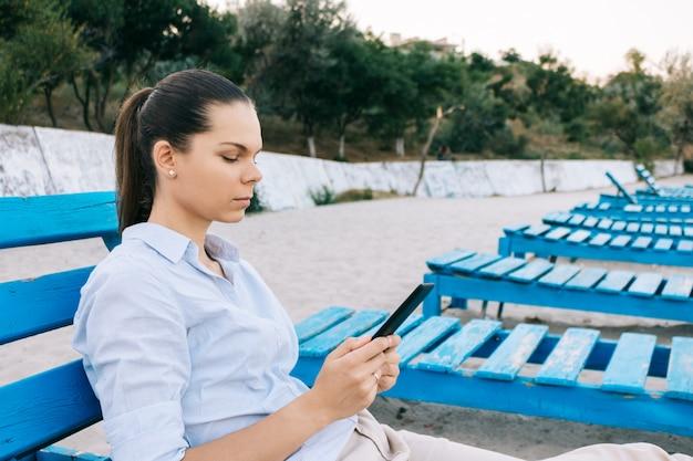 Seitenansicht einer jungen frau am strand liest ein buch auf der bank sitzen