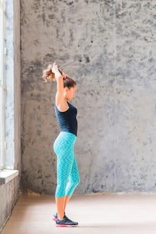 Seitenansicht einer jungen Frau der Eignung, die gegen die Betonmauer steht, die ihr Haar bindet
