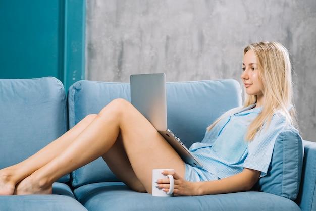 Seitenansicht einer jungen frau, die auf sofa unter verwendung des laptops sitzt