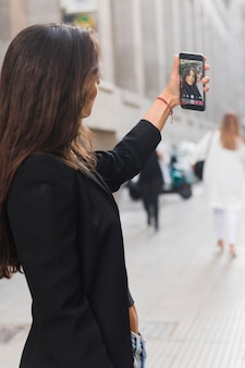 Seitenansicht einer jungen frau, die selfie auf smartphone in der stadt nimmt
