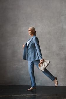 Seitenansicht einer jungen frau mit blondem haar im blauen anzug und mit der stilvollen geldbörse, die drinnen aufwirft