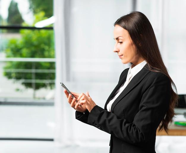 Seitenansicht einer jungen geschäftsfrau, die smartphone verwendet