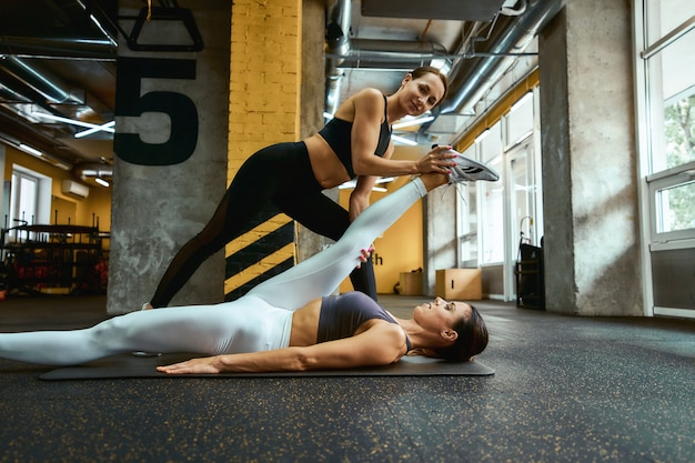 Seitenansicht einer jungen schönen fitnessfrau in sportbekleidung, die auf einer yogamatte im fitnessstudio liegt und mit hilfe ihres personal trainers dehnübungen macht. sport und gesunder lebensstil