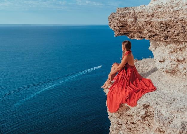 Seitenansicht einer jungen schönen sinnlichen frau in einem roten langen kleid, die auf einem felsen hoch über dem meer posiert