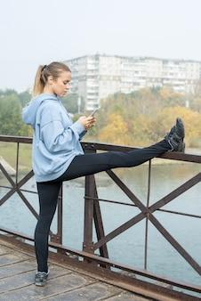 Seitenansicht einer jungen zeitgenössischen sportlerin, die mit gestrecktem rechten bein auf metallzaun auf der brücke steht und im smartphone scrollt