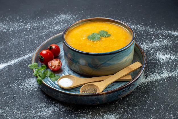 Seitenansicht einer köstlichen roten linsensuppe in einer schüssel, serviert mit grünem tomaten-pfeffer-salz auf blauem tablett auf schwarz-weißem hintergrund mit freiem platz