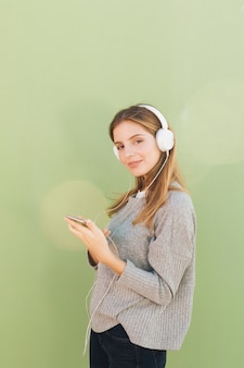 Seitenansicht einer lächelnden hörenden musik der jungen frau auf kopfhörer gegen grünen hintergrund