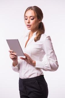 Seitenansicht einer lächelnden zuversichtlichen frau stehend und unter verwendung der digitalen tablette lokalisiert gegen graue wand