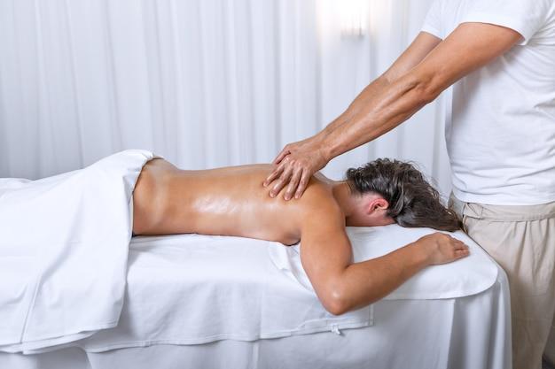 Seitenansicht einer latina-frau, die mit dem gesicht nach unten liegt, während der therapeut im wellnessbereich rückenmassage macht. konzept des spas.