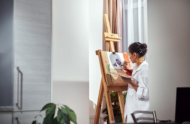 Seitenansicht einer malerin mit gesammelten haaren in einem brötchen und pinseln in ihren haaren, die vor der staffelei in werkstatt und zeichnung stehen