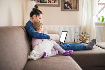 Seitenansicht einer Mutter, die mit ihrer Tochter unter Verwendung des Laptops sitzt