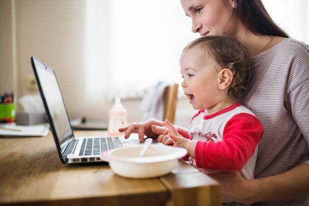 Seitenansicht einer mutter mit ihrem baby, das laptop verwendet