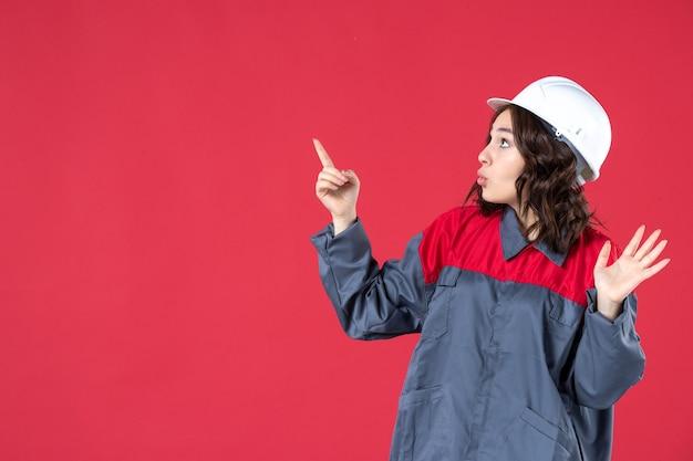 Seitenansicht einer neugierigen baumeisterin in uniform mit schutzhelm und nach oben auf isoliertem rotem hintergrund zeigend