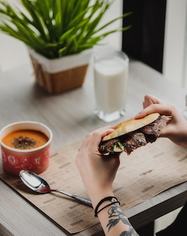 Seitenansicht einer person, die döner kebab im fladenbrot am tisch isst