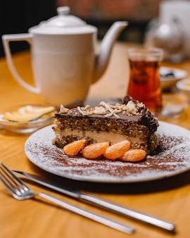 Seitenansicht einer scheibe schokoladenkuchen mit vanillecreme und nüssen, serviert mit mandarinenscheiben auf einem weißen teller